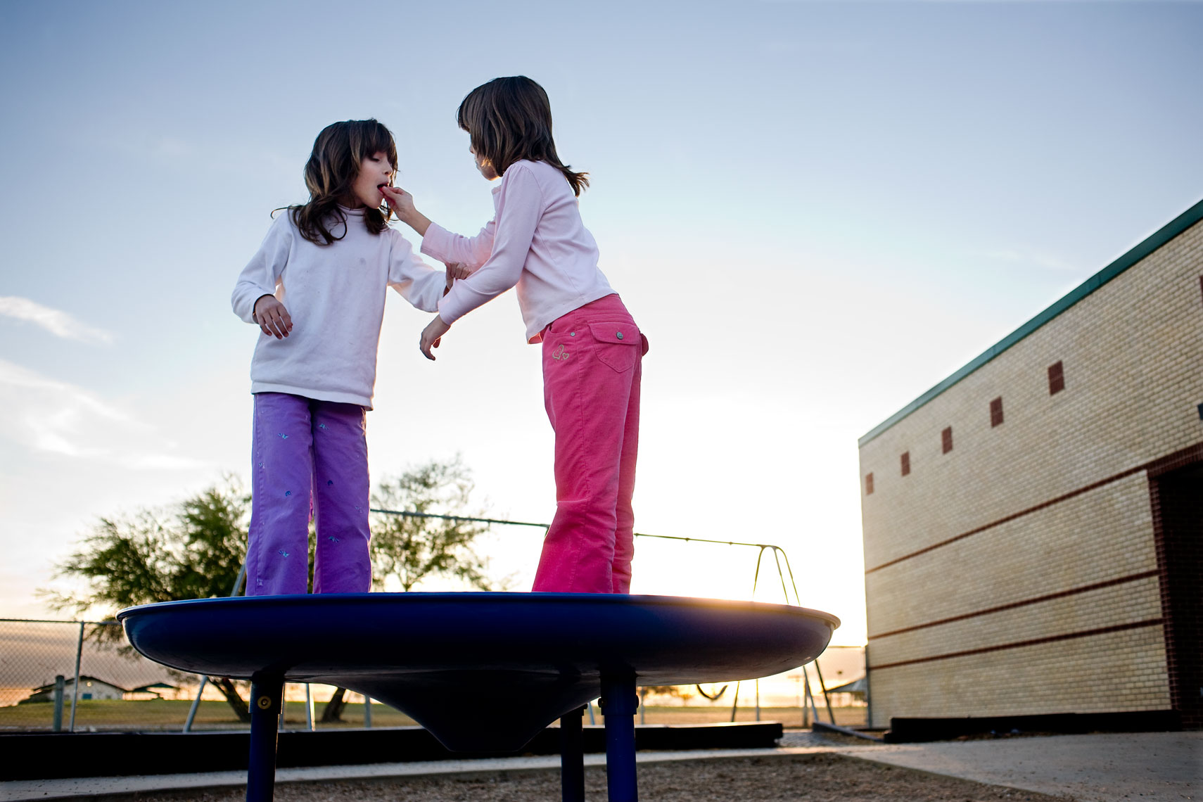 twin girls standing on school playground for washington dc photojournalism