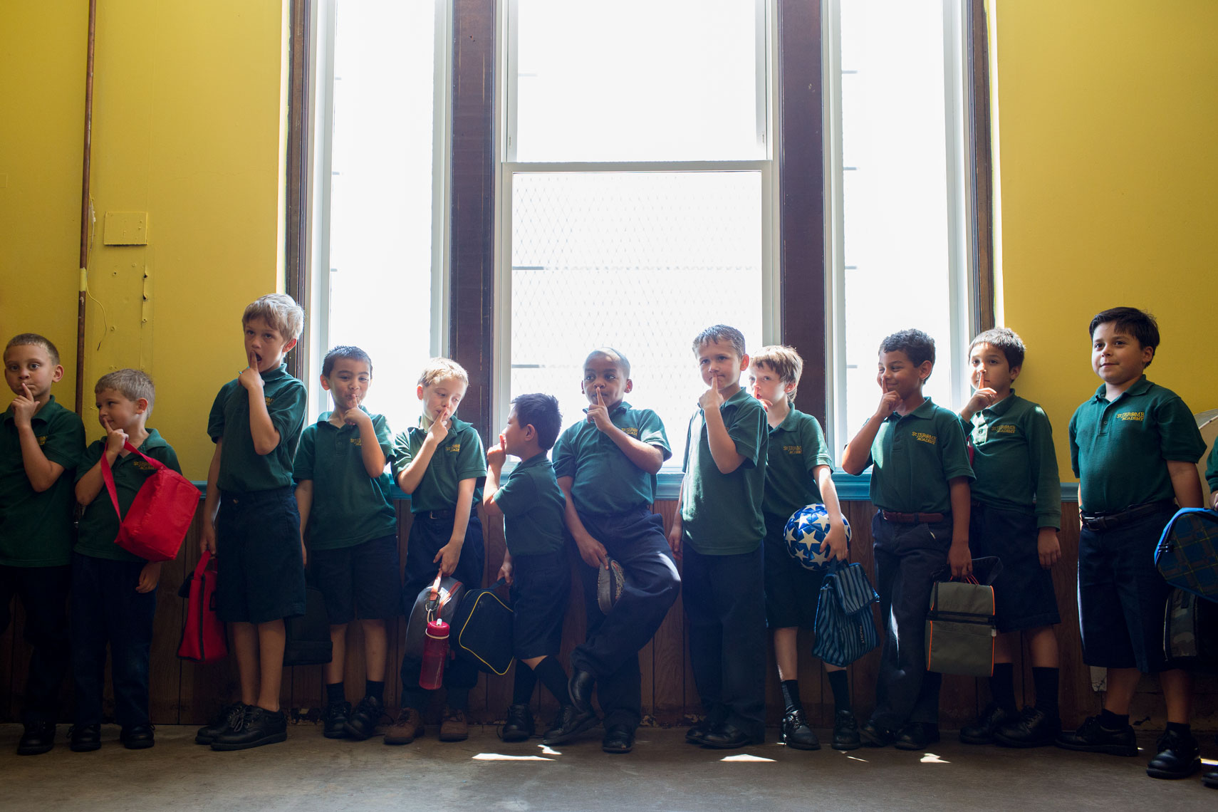 school boys lining up by window for washington dc photojournalism