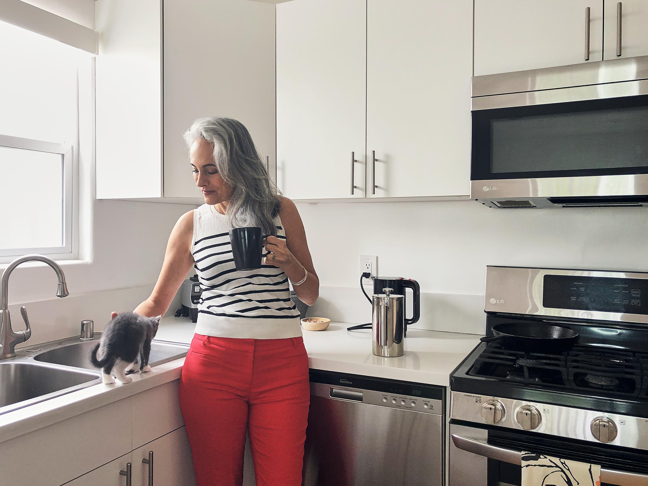 woman with silver hair in kitchen, remote photography