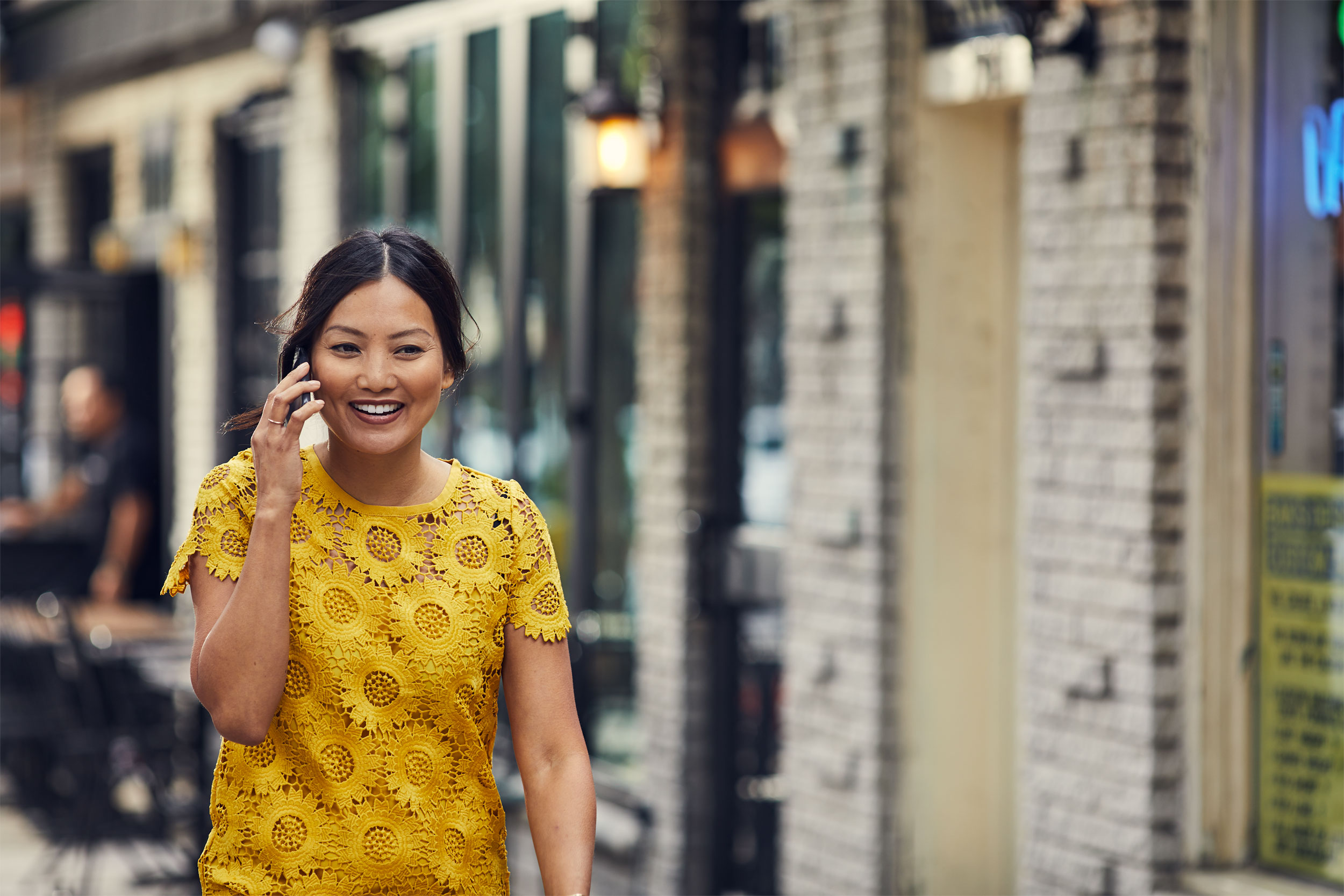 woman in yellow dress talking on smartphone on street, washington dc commercial photography